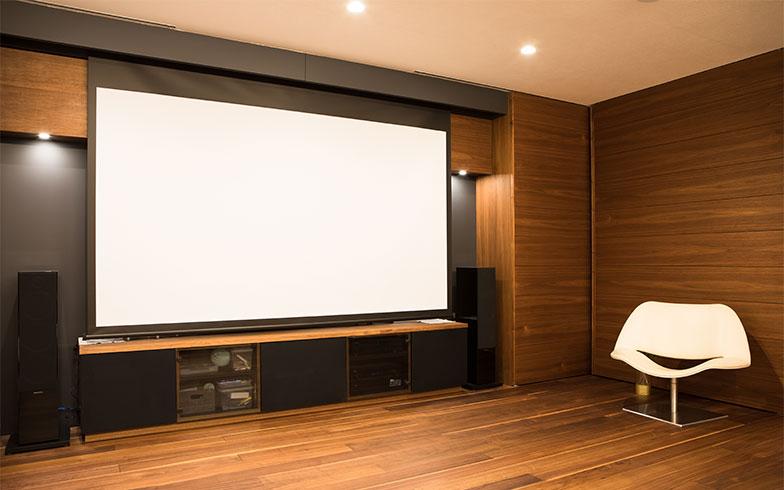 65インチの大型テレビの前に、120インチのスクリーンが下りて来ると大迫力のシアタールームになる(写真撮影/片山貴博)