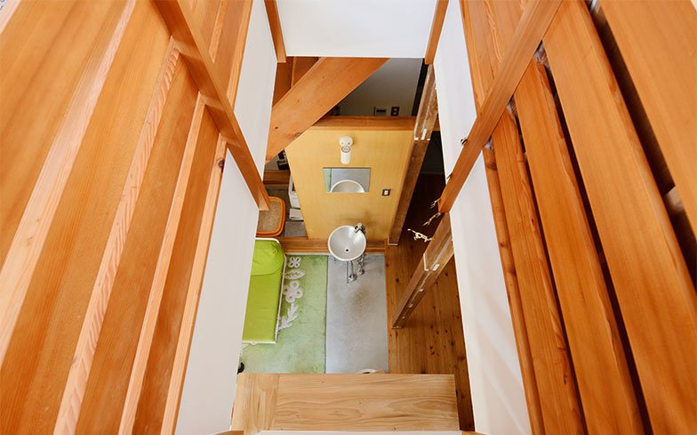 2階から吹抜けを覗くと、真下に洗面台が見えます。洗面台の裏側は洗濯機置き場、その奥がバスルーム、反対側の廊下奥にはトイレ。どこにいても声をかけやすい間取りです(写真撮影/内海明啓)