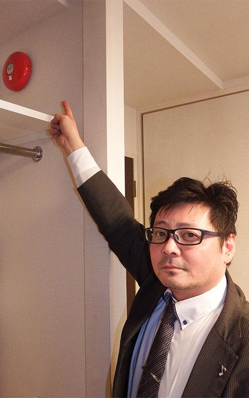 山下さんが指差す先には非常ベル。共用スペースではなく、各部屋に取り付けられている。山下さんはロックバンドのドラマーだった経験をもつ(写真撮影/織田孝一)
