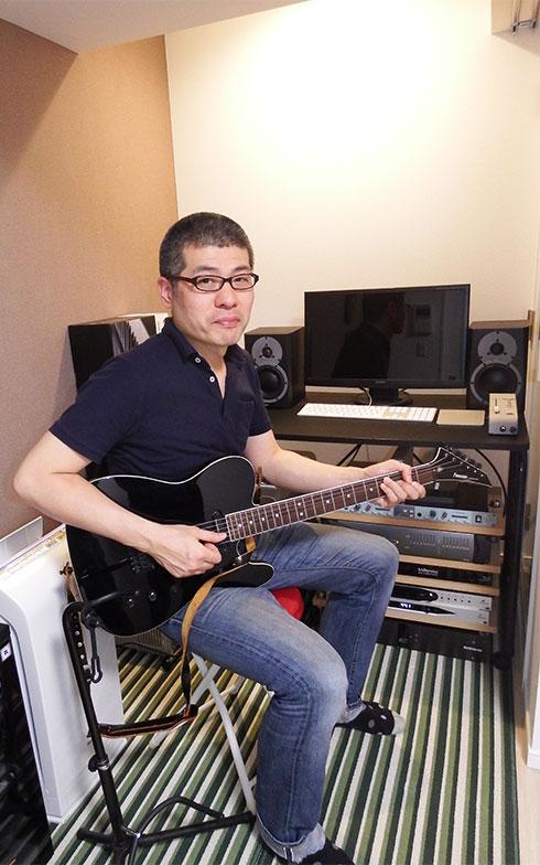 趣味のギターを手に、音響エンジニアの久保浩巳さん。自動車整備士だったが音楽好きが高じて音響エンジニアに転じた(写真撮影/織田孝一)