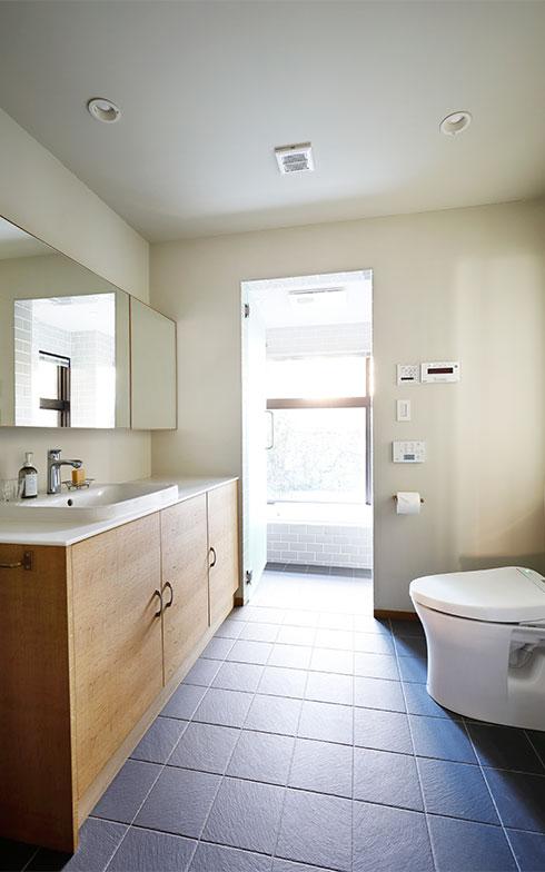 ペーパーホルダーやキャビネットの取っ手なども同色、同じ質感でそろえた。バスマットもなく、余計な物を一切置いていないため、洗面室と浴室がいっそう広く感じられる(写真撮影/菊田香太郎)