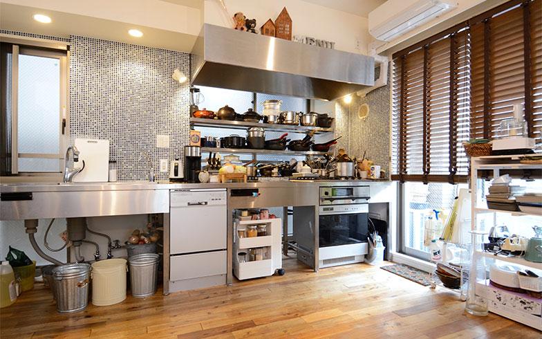 """シンクやコンロを壁側に寄せて、""""見せる収納""""にこだわったキッチン。ブルーのタイルがステンレスの風合いとマッチして、清潔感のある雰囲気を醸し出しています(写真撮影/内海明啓)"""