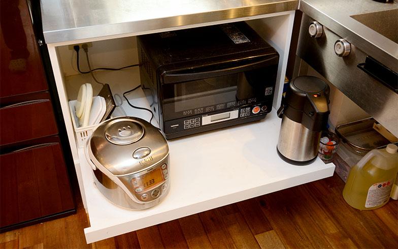 奥行と幅のある収納スペースに電子レンジや炊飯器、電気ポットをセットイン。使用時にトレイを引けば、湯気で収納家具を傷めることはありません(写真撮影/内海明啓)