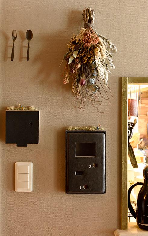 左のインターホンはベニヤ板で囲い、表面をアイアン塗料で黒くして、上部にミニチュアを飾っています。「1」「2」と書かれた横の丸い押しボタンはレザー貼り。左側にある床暖房の操作パネルは黒い蓋を付けました。(写真撮影/山出高士)