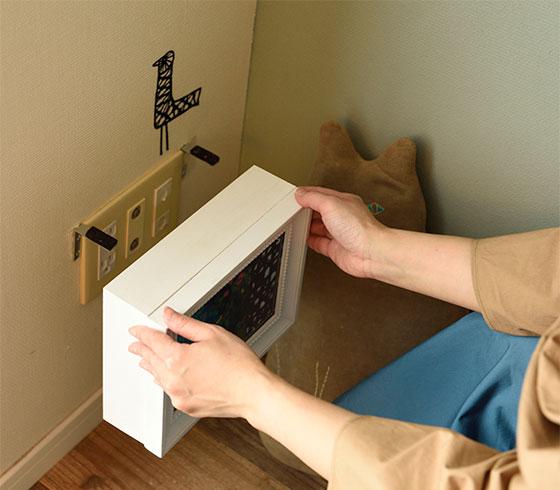 コンセントの両脇にL字フックを取り付けて、アートフレームを貼ったボックスを引っ掛けるだけ。ボックスの下側はコードが出るように空けてあります(写真撮影/山出高士)