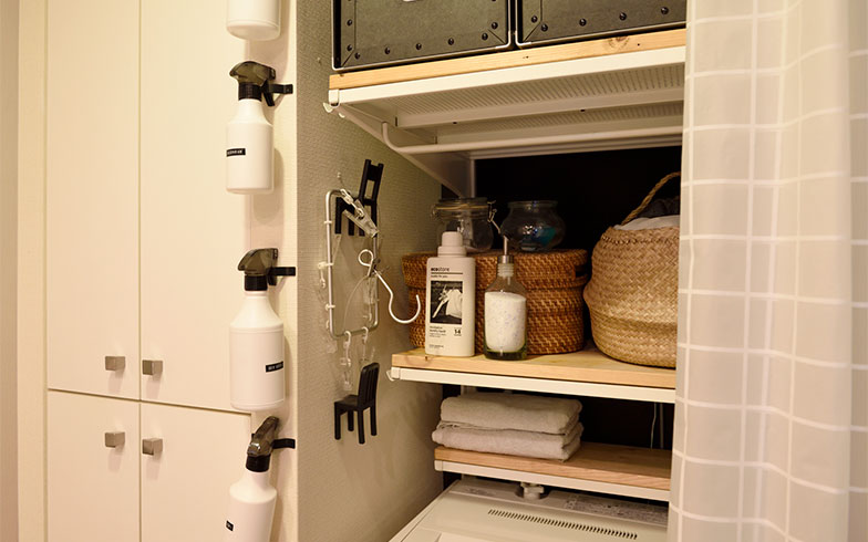 洗面室の壁に洗剤ボトルをかけられるよう、扉の取っ手をフックとして取り付けました。パッと手に取れて便利。普段はカーテンを閉めてスッキリ隠しています(写真撮影/山出高士)