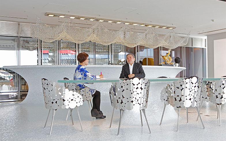 ガラステーブルと後ろにあるキッチンカウンター、壁のミラーと共に楕円の有機的なデザインが、未来的な空間に柔らかさを添える(写真撮影/糠澤武敏)