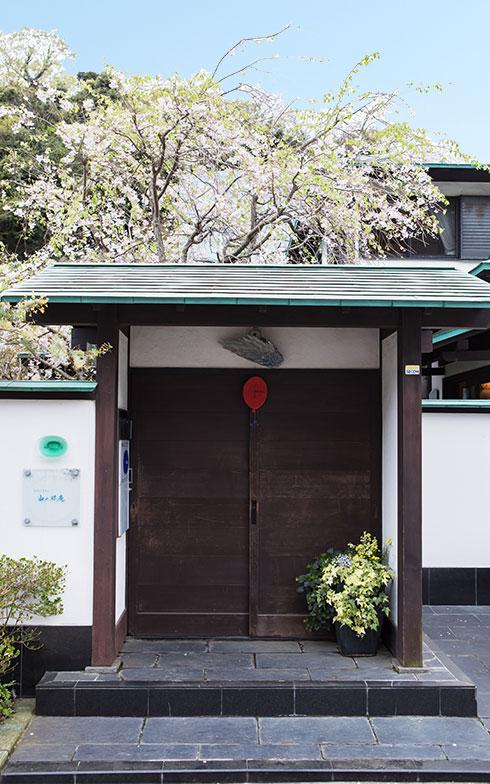 庭の桜を背景にたたずむ門扉。正面の飾りや手前の鉢植えは季節毎に替わり、道ゆく人を楽しませてくれる(写真撮影/片山貴博)