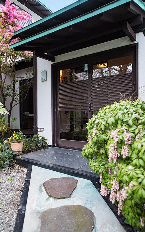 庭の花を愛でながら、自然石のアプローチを進む。木の造作が施されたガラス引戸(写真撮影/片山貴博)