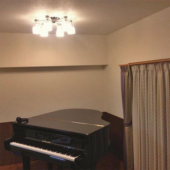 カーテンは色味としてはシックで、光沢感のない無地の生地を使用し、ピアノに合ったシンプルなものを選択、ピアノの上のシャンデリアも、シャープでスッキリしたデザインのものに(画像提供/水田恵子さん)