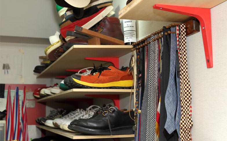 出番待ちの靴や衣類を大量に収納するクローク。靴の高さに合わせてIKEAで購入したパーツと板でDIY、木製のネクタイ掛けはBROOKS BROTHERSのショップで使われていたものをDIYした(写真撮影/飯田照明)