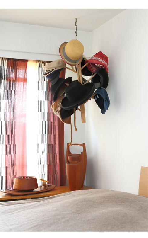 上階寝室の窓際には、DIYで天井から帽子掛けを吊るして見せる収納に(写真撮影/飯田照明)