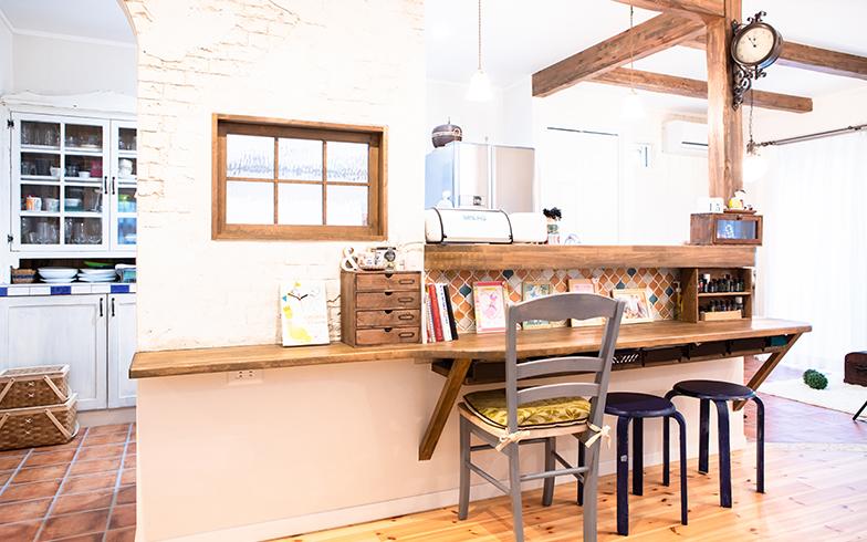カウンターキッチンは、今は子どもたちの勉強スペースになっている。白い漆喰の壁、木の柱やカウンター、柱に付いているアンティーク風の時計が、ナチュラルで優しい印象を醸し出す(写真撮影/片山貴博)