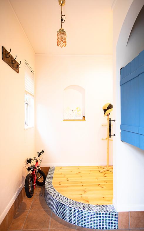 青い扉とタイルの映えるエントランス。多くの来客があっても靴がたくさん置けるように、あえて上がりの部分は半円形に(写真撮影/片山貴博)