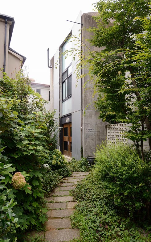 石畳のアプローチは、まるで駒沢公園と家をつなぐ小道のよう。「このアプローチが少しカーブを描いていて、家全体が外から見えないところがいいですね」とSさん(写真撮影/内海明啓)
