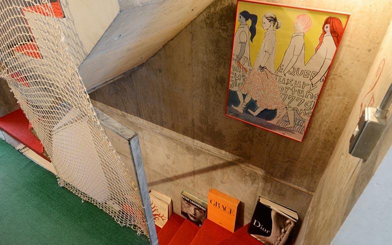 階段周辺のインテリアも個性的。赤い絨毯(じゅうたん)に洋書が並べられたスタイリッシュなスペースのすぐそばには、これまた公園仕様のネットが掛けられています(写真撮影/内海明啓)