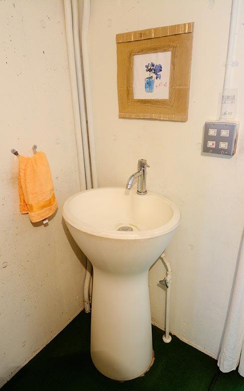 階段を上がったところの洗面台も、公園の水飲み場のよう。この洗面台は、イタリアのバスブランドagapeのもの。段ボール製の額縁に入れて飾られたお子さんの絵もアーティスティック(写真撮影/内海明啓)