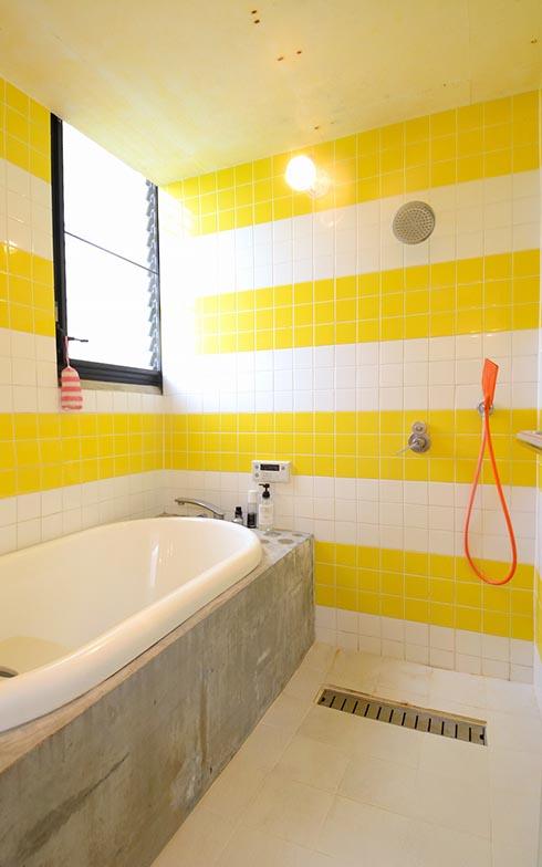 ビビッドなイエローのタイルが陽気な雰囲気を醸し出すバスルーム。オレンジ色のシャワーは、洗面台と同じくイタリアのバスブランドagapeのもの(写真撮影/内海明啓)