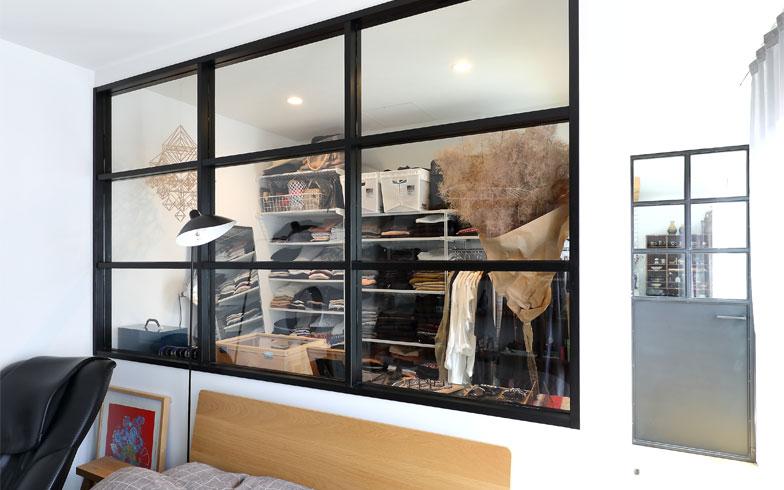 LDKと寝室を仕切るドア(写真右手)も新潟で特注した鉄製。ウォークインクローゼットのガラス窓は鉄製のドアと似たデザインで、素材の木枠を黒の塗装にしてコストダウン(写真撮影/飯田照明)