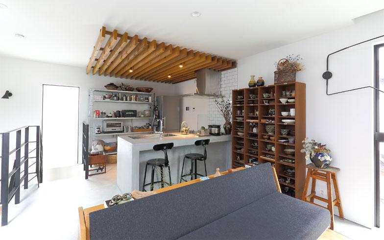 左手がこだわりの鉄製階段の手すり。2階のLDKはモルタルで造作したオープンキッチンの開放的な空間。ワンルームのLDKのなかでキッチン部分は天井に木を用いてコーナーを区切っている。オープンな大空間のなかでコーナーごとに素材で変化をつけるテクニックは店舗設計で学んだという(写真撮影/飯田照明)