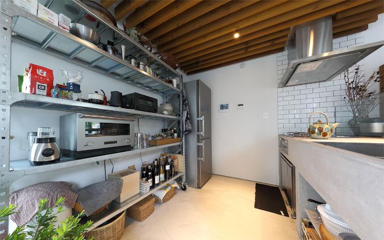木の天井にステンレスやモルタルの厨房機器や収納棚で素材をまとめたキッチンスペース。調味料や調理道具類も全て見せる収納だが、素材や色がそろっているのでスッキリ見える(写真撮影/飯田照明)