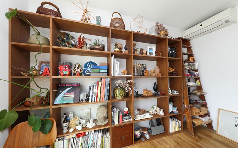 寝室の収納もオープンな見せる収納。収納棚とデンマーク製アンティーク脚立の素材を木であわせているので統一感がある(写真撮影/飯田照明)