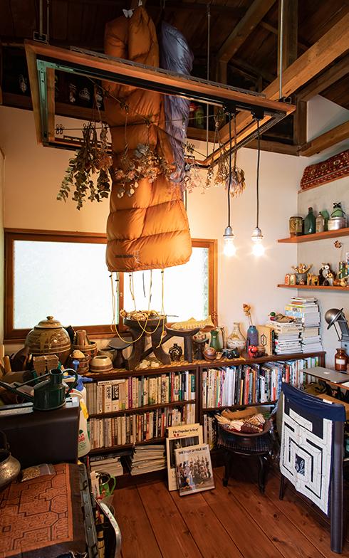 玄関の上など天井裏は全て収納スペースに。かさばるシュラフは天井から吊るして見せて収納。まるでアウトドアショップの展示のようなこのコーナーには物を雑然と、間隔も狭くたくさん置いている(写真撮影/片山貴博)