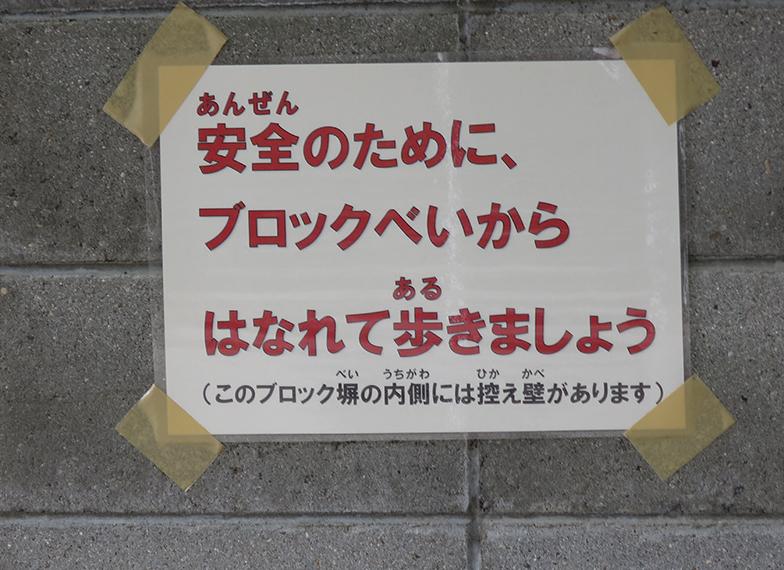 学校施設のブロック塀に張られた注意を促す告知(写真撮影/コハマジュンイチ)