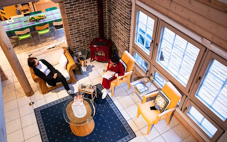 ログの構造壁にタイルの床、赤い薪ストーブのある吹抜けのリビング(写真撮影/片山貴博)