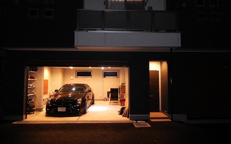 夜のエスパース外観(実際には夜間にガレージを開けることはほとんどないが、開けていただいた)。シックな外観やガレージの広さがよくわかる(写真撮影/織田孝一)