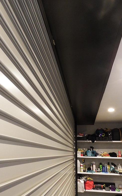 電動シャッターのあるガレージ入口。上の黒い部分に扉が巻き取られるため、開けたときに照明が隠れるようなことがない。奥に見える作り付けの棚は非常に便利(写真撮影/織田孝一)