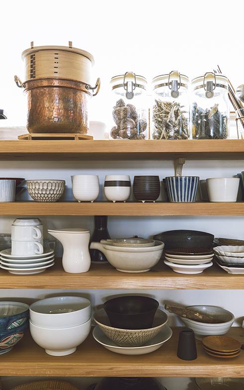 食器棚は大きめの鉢のサイズに合わせて奥行きを設定。店で扱う器や銅なべ、せいろなどもあり、使い込まれた様子を見せてもらうことができる(写真撮影/嶋崎征弘)