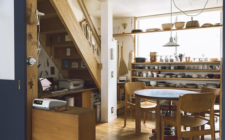階段の下に天板を置き、坂本さんの事務スペースに。店からは目に入りにくい場所なので、多少ものが多くても気にならない。階段裏には吟ちゃんが描いた絵などを貼って楽しい雰囲気に(写真撮影/嶋崎征弘)