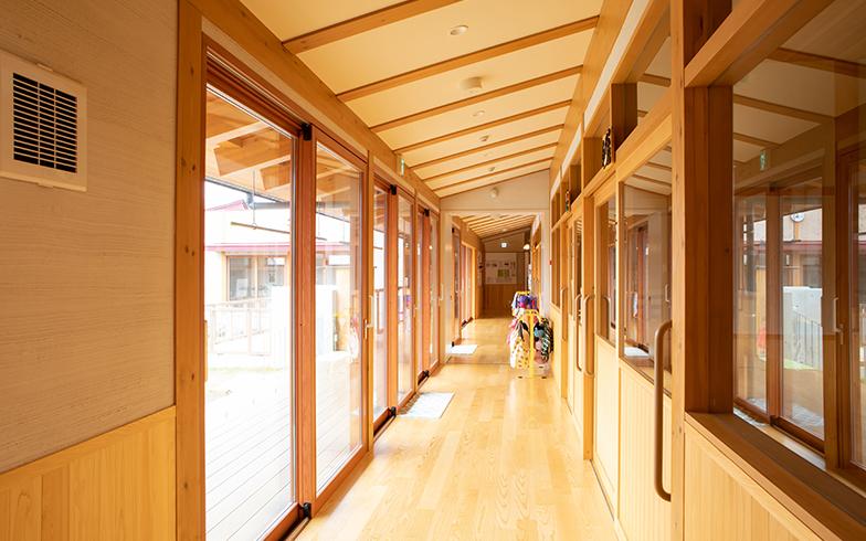 保育棟の廊下。左側の開口部には遮音性の高い木製サッシが使われている。屋根の形を生かした勾配天井は空間を広く見せる効果も(写真撮影/片山貴博)