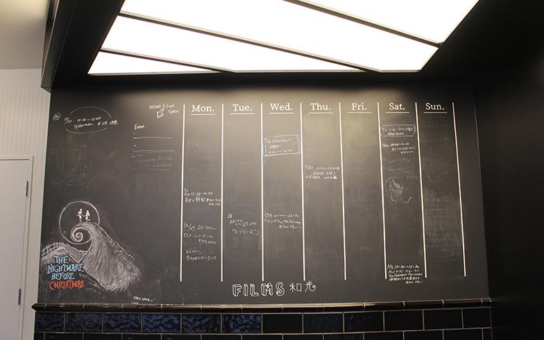 シアター入口には予定表が。すべての共用部は、貸切や占有はNG。ボードに使いたい時間を書き、観たい人がいたら一緒に参加も可能。映画館もコミュニケーションの場所のひとつ(写真撮影/SUUMOジャーナル編集部)