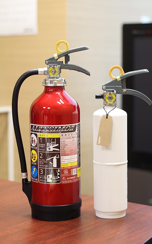 左がモリタ宮田工業製の業務用消火器で約3.9kg、右が「+maffs」の「+住宅用消火器」。「+住宅用消火器」は約2.2kgとコンパクトで、部屋に置いても圧迫感がない(写真撮影/SUUMOジャーナル編集部)