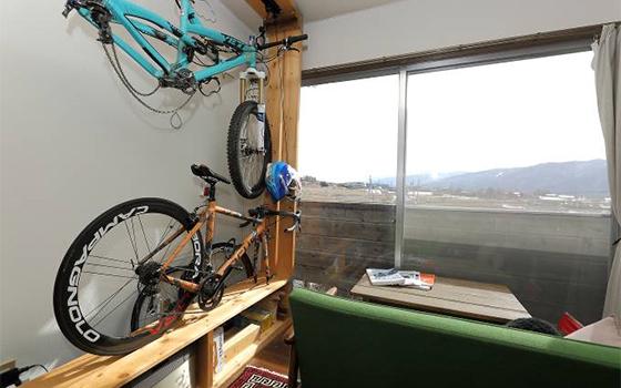 蓼科の住まいは18平米のワンルーム。壁は夫がDIYでつくった木製棚。趣味のマウンテンバイクやアウトドアグッズなどの収納になっている。窓からは八ヶ岳連峰の景色が一望できる(写真撮影/飯田照明)
