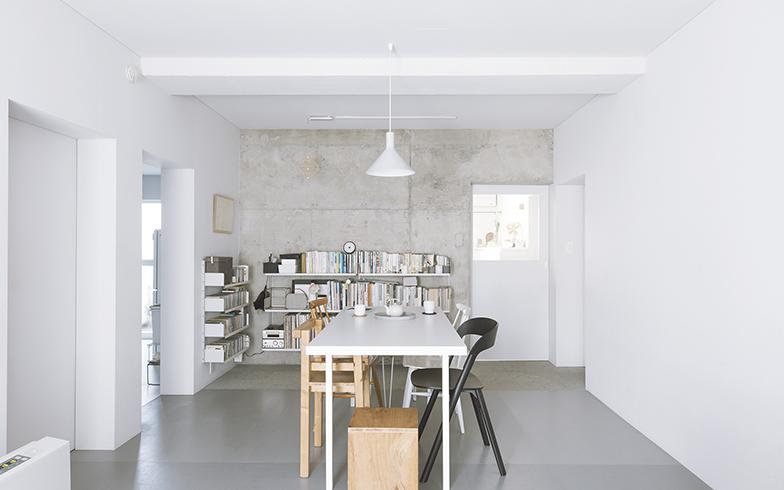 ダイニングでは、壁付けの棚だけを収納スペースに。夫婦それぞれが大切に長く持ち続けたい本を厳選している。右側の壁は何も飾らずにスッキリしていて広さを感じさせる(写真撮影/嶋崎征弘)