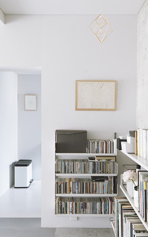 リビング・ダイニングでは、本のほかに、CDもこの棚に収まるだけにしているそう。上部には絵を一枚かけているが、そのほかの壁に何も飾っていない。収納と装飾、そして余白のバランスを取っていることがよく分かる。「これくらい限られたスペースの壁なら、何か飾ってもバランスが取りやすい気がします」(写真撮影/嶋崎征弘)
