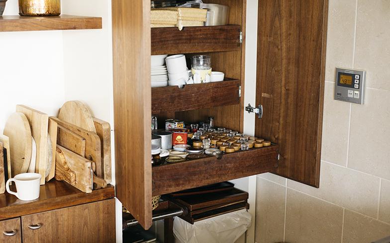収納スペースの下部には扉をつけず、ゴミ箱置き場に。凹みにゴミ箱を置くと目立たないうえ、調理中の動きの邪魔になりません。キッチンの床が掃除しやすくなるというメリットも(写真撮影/嶋崎征弘)