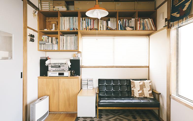 仕事スペースの対面にあるリビング。上部に棚を配したおかげでソファを置くことができた。棚や壁には民芸品が飾られていて、二人が日常的に楽しんでいることが分かる(写真撮影/嶋崎征弘)