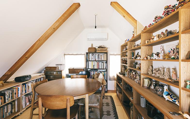 三角屋根の一軒家ということが分かる屋根裏部屋。左の本棚はYUYAさんがサイズに合わせて自作したもの。キャスター付きなので奥のものも取り出しやすい(写真撮影/嶋崎征弘)
