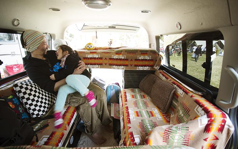 後部座席はソファ仕様にしてくつろげるスペースに。寝る際はシートの背もたれを中央にはめ込んでフルフラットに、さらにソファの上に板を渡して2段ベッドにもできる(撮影/相馬ミナ)