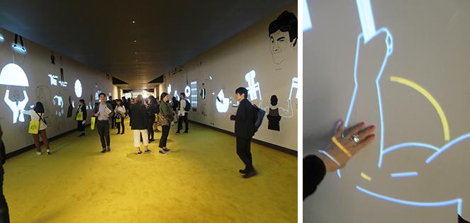 黄色の丸ゾーンに手を置くと、センサーで動き出すデザイナー。インタラクティブなプレゼンテーションが今っぽい(写真撮影/藤井繁子)