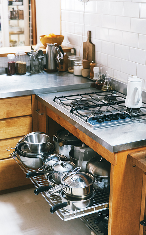 重さのある鍋類は、出し入れしやすいようスライド式の棚板に。リフォーム時に伝えてつくってもらったもの(写真撮影/嶋崎征弘)