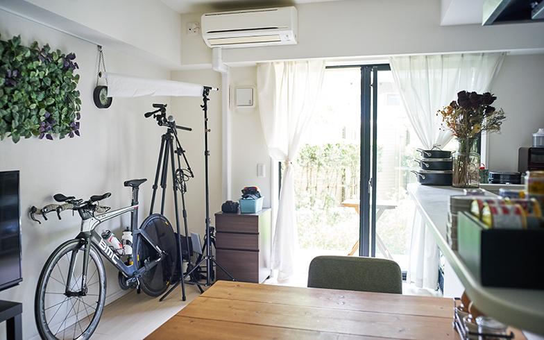 リビングの片隅には本格的なトライアスロンバイクのほか、YouTubeの動画チャンネル「Cooking Athlon(クッキングアスロン)」用の撮影機材も。壁に飾ったIKEAのアートプラント「FEJKA(フェイカ)」が爽やかな印象(写真撮影/相馬ミナ)