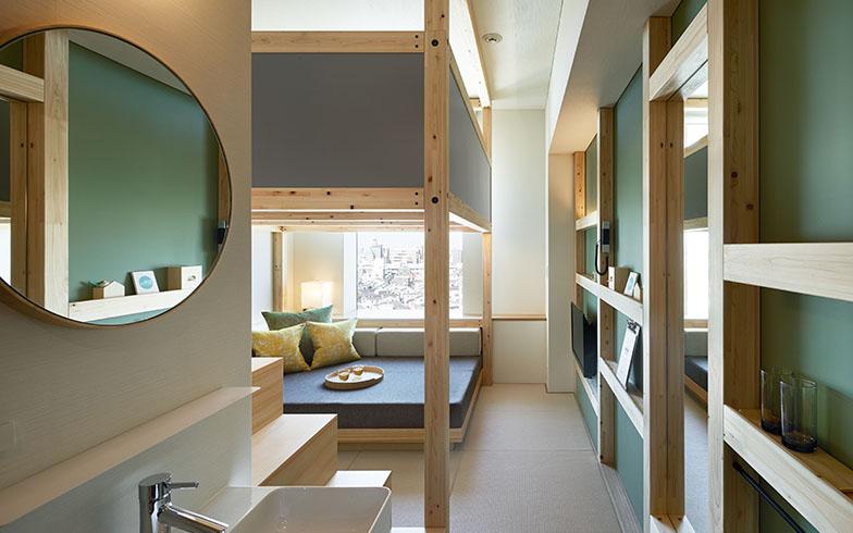 客室は約19平米とコンパクトながら、天井高は3m近くあります。やぐらにベッドを置いて、その下に大きなソファを配したり、壁面に角材を組んで収納スペースにしたりと、空間を使い切る工夫が満載(写真提供/星野リゾート)