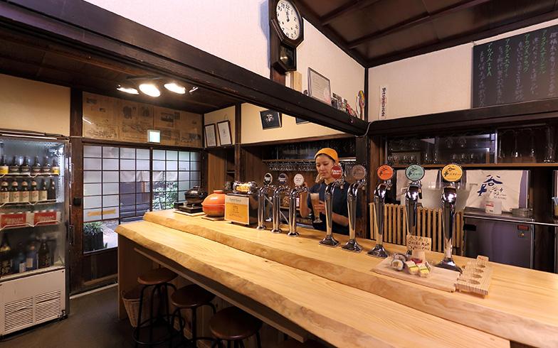 「谷中ビアホール」代表取締役の吉田瞳さん。店内は昭和初期の風情を残すしつらえになっている。このカウンターは、ドラマ「僕とシッポと神楽坂」でコオ先生(相葉雅紀)が友達と飲む居酒屋としても使われた(撮影:飯田照明)