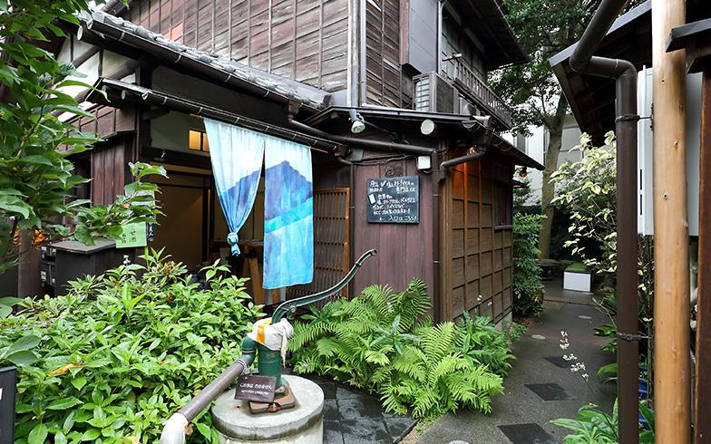 井戸の右手があたり2。暖簾をくぐると「おしおりーぶ」の店内に行ける(撮影:飯田照明)