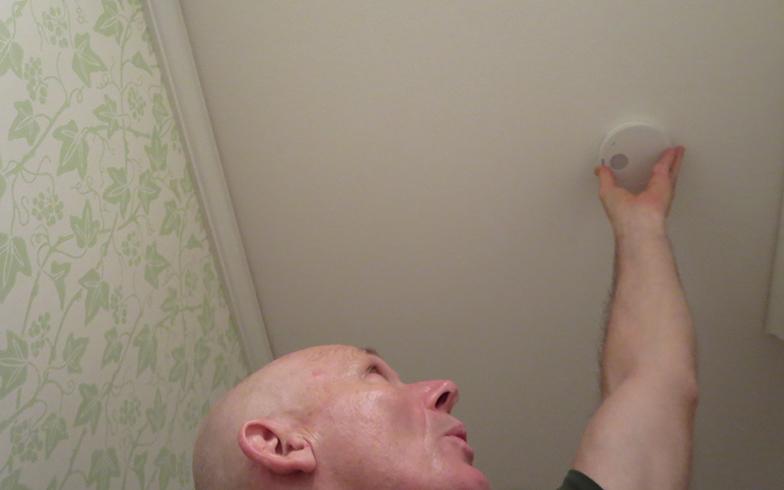 さっそく、筆者宅でも寝室に火災警報器を設置。製品に同封のネジを天井に2カ所留めるだけ。ボタンを押して作動確認!(写真撮影/藤井繁子)